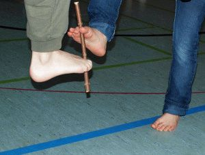 Передача палки ногами